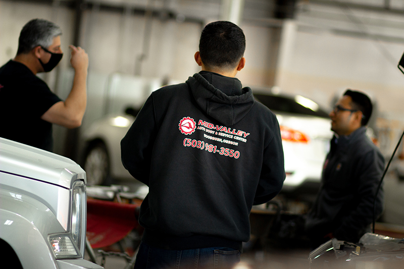 Group of three mechanics talking together in a large industrial garage